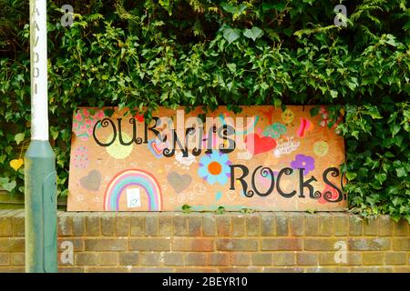 16th April 2020, Southborough, Kent, UK: Child's drawings of a rainbow, hearts and Our NHS Rocks message for NHS staff and key workers on a plywood board outside a hedge in residential area during the government imposed quarantine / lockdown to reduce the spread of the coronavirus. Children across the country have been putting drawings of rainbows in windows to spread hope and encourage people to stay cheerful during the pandemic.