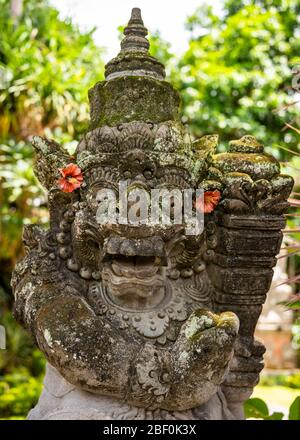Vertical close up view of a gate guardian statue at Ubud palace in Bali, Indonesia.