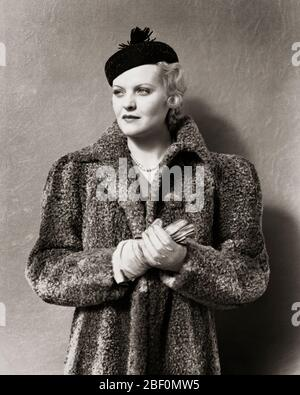 1930s 1940s UNSMILING BLONDE WOMAN WEARING BLACK PILLBOX STYLE HAT WITH TASSEL AND A GRAY PERSIAN LAMB FUR COAT LEATHER GLOVES - f7987 HAR001 HARS LUXURY WOOL COPY SPACE HALF-LENGTH LADIES PERSONS CONFIDENCE EXPRESSIONS B&W LAMB DREAMS STYLES AND TASSEL PILLBOX PRIDE STYLISH STRAND FASHIONS GRAY MID-ADULT MID-ADULT WOMAN PERSIAN BLACK AND WHITE CAUCASIAN ETHNICITY HAR001 OLD FASHIONED PERSIAN LAMB UNSMILING