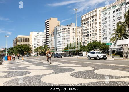 Father and daughter riding a bike on Copacabana boulevard with typical Portuguese tiles pattern during the COVID-19 Corona virus outbreak