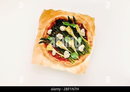vegan pizza with asparagus and artichokes, served on the table for family or friends. Healthy lunch or dinner. - Stock Photo