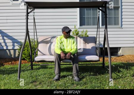 A portrait of an African-American man sitting outdoors on a  patio swing  in a backyard and sad - Stock Photo