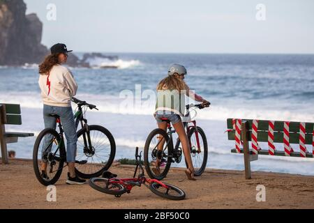 Two teenage girls riding bicycles at the beach in Sydney during covid 19 lockdown with benches taped off to prevent people loitering,Sydney,Australia - Stock Photo