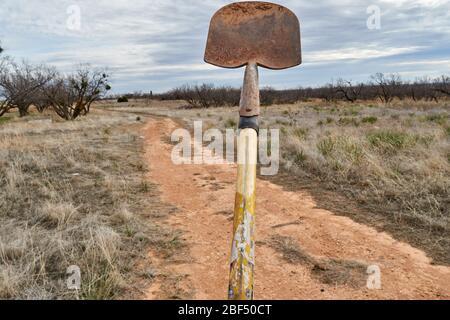 Old dirty shovel isolated on Texas desert background - Stock Photo