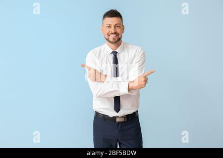 Businessman pointing in different directions on color background. Concept of choice - Stock Photo