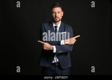 Businessman pointing in different directions on dark background. Concept of choice - Stock Photo