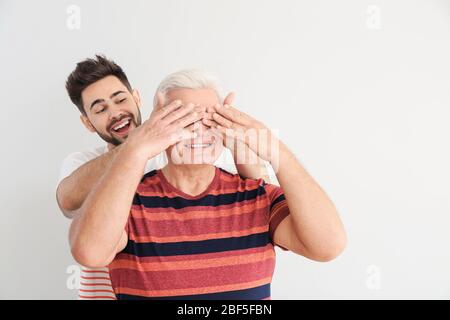 Young man and his father having fun on light background - Stock Photo