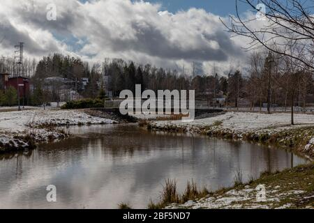 Suburban neighbourhood with light snow in Finnish spring with no people - Stock Photo