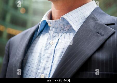 Close-up of unrecognizable businessman in dark pinstripe suit and unbuttoned shirt collar standing outdoors in an office building courtyard - Stock Photo