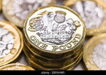 LONDON, UK - APRIL 2019: Close up view of British currency GBP - One Pound coin surrounded by other coins - Stock Photo