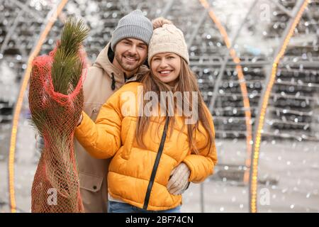 Young couple with bought Christmas tree outdoors