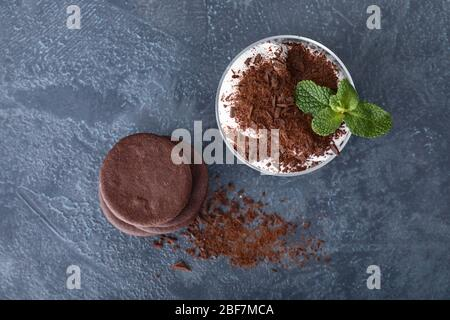 Tasty chocolate cookies with dessert in glass on dark background - Stock Photo