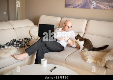 mature man using laptop and playing with cute cat on sofa at home during quarantine of coronavirus covid-19