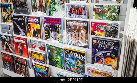 Comic books on the display shelf at a local comic store. - Stock Photo
