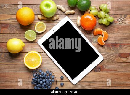 Tablet computer with healthy products on wooden background