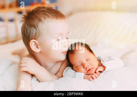 Happy little brother with newborn baby lying in a bed together, kissing and hugging. Siblings. New born baby sleeping and two years old brother togeth - Stock Photo