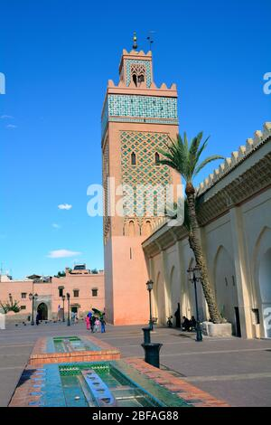 Marrakesh, Morocco - November 22nd 2014: Unidentified people and mosque with minaret in traditional style - Stock Photo