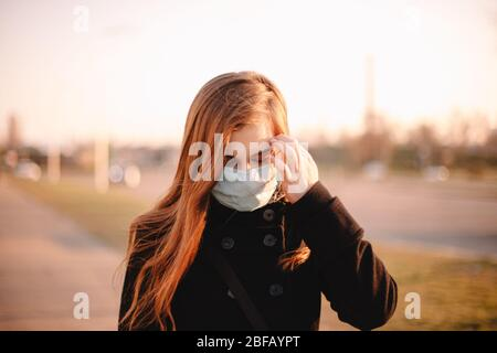 Portrait of young woman wearing protective face medical mask while walking on street in city - Stock Photo