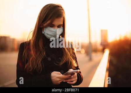 Young woman wearing protective face medical mask using smart phone while standing on bridge in city at sunset - Stock Photo