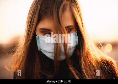 Close up portrait of sad depressed young woman wearing protective face medical mask while standing in city during sunset - Stock Photo
