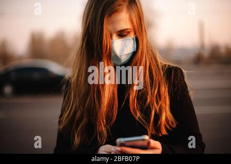 Portrait of young woman wearing protective face medical mask using smart phone while standing on street in city at sunset - Stock Photo