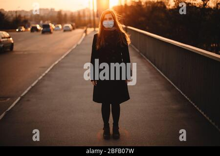 Portrait of young woman wearing protective face medical mask while standing on empty sidewalk on bridge in city during sunset - Stock Photo