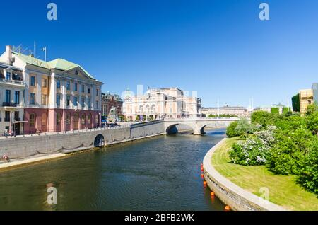 Sweden, Stockholm, May 31, 2018: Royal Swedish Opera house Kungliga Operan building across the bridge with green bushes and grass lawn foreground in c - Stock Photo