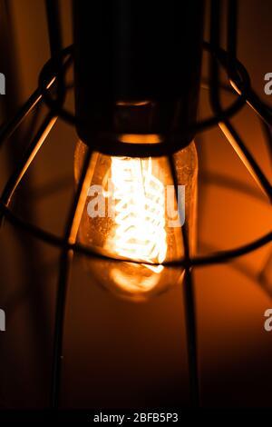 Vintage orange Edison incandescent light bulb in an old lamp lantern - Stock Photo