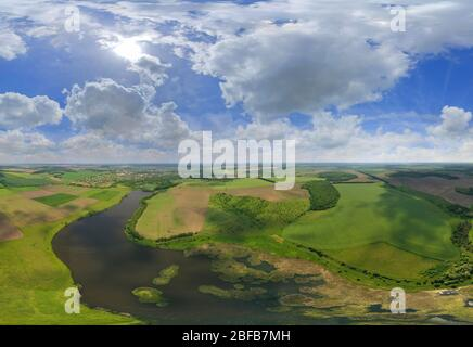 The countryside. Unrealistically beautiful nature is photographed from the sky. Many white soft clouds in the blue sky. Panorama of nature and wide fi - Stock Photo