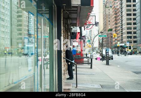 A man looking in a closed restaurant window during the COVID19 pandemic in New York City. - Stock Photo