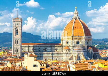 Top aerial panoramic view of Florence city with Duomo Cattedrale di Santa Maria del Fiore cathedral, buildings houses with orange red tiled roofs and