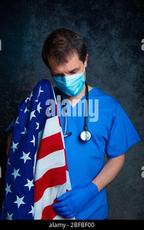 Sad/pensive, male doctor in blue hospital scrubs with face mask and stethoscope, holding the Stars & Stripes American flag close to his chest.