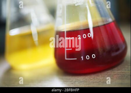 Two Erlenmeyer flasks containing unknown yellow and red liquid