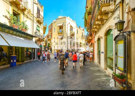 Tourists shop the main street Corso Umberto in old town Taormina on a warm summer day in Sicily, Italy - Stock Photo