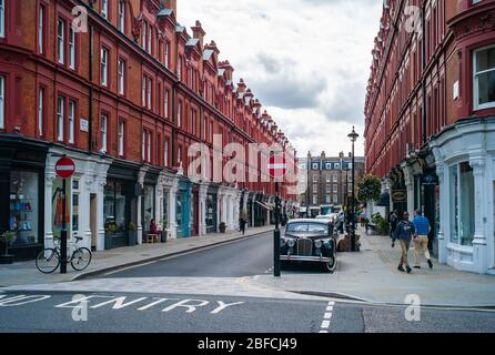 London, England, United Kingdom, May 24 2016: Chiltern Street with Rows of Shops in Old Red Brick Buildings. A Shopping Street in Marylebone, London, - Stock Photo