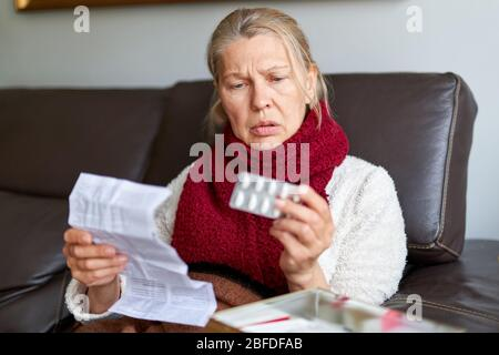 Woman Mature Taking Medicine. Woman Holding Blister Pack With Pills In Hand And Reading Medical Instructions. Woman elder Looking At Instruction, Hold - Stock Photo