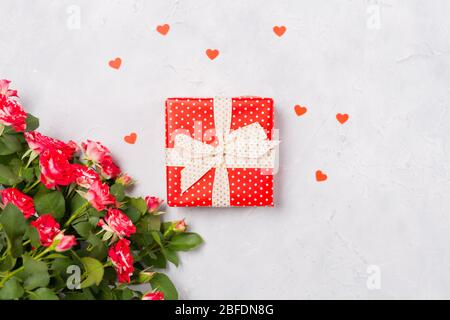Red gift box and red roses on white background with red heart confetti. Christmas present, valentine day surprise, birthday mother's day concept. Flat - Stock Photo