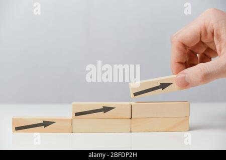 Successful business concept - hand puts wooden blocks with arrows on a white background. Close up. Stock Photo