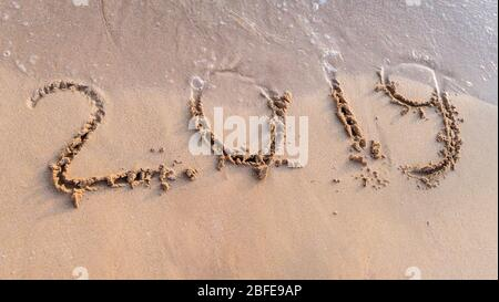 New Year 2019 written on sand beach and ocean wave. lettering on the beach. Happy New Year 2020. - Stock Photo