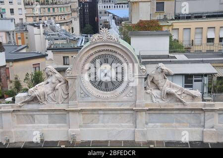 Around Italy - A clock face on a building to the rear of the Duomo in Milan Stock Photo