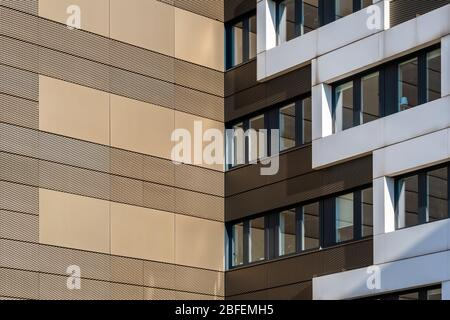 Golden building facade cladded with punched and perforated metal sheets - Stock Photo