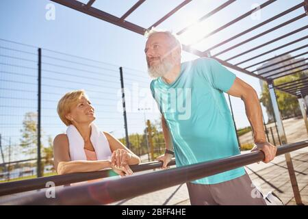 Senior family working out at outdoor gym. Mature bearded man in sportswear doing push ups on parallel bars. Active senior couple exercising in the - Stock Photo