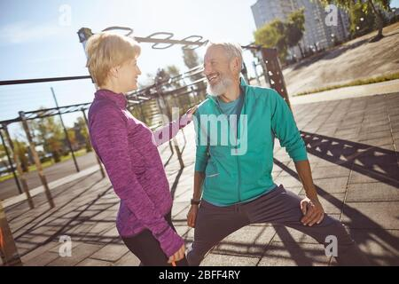 Happy and healthy. Smiling mature family couple in sportswear doing gymnastics together at outdoor gym. Man and woman doing stretching exercises - Stock Photo