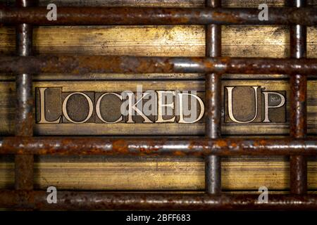 Photo of real authentic typeset letters forming Locked Up text behind rusty bars on vintage textured grunge copper and gold background