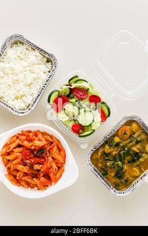 takeaway food in disposable containers: rice, vegetable curry, Italian pasta with tomato sauce and fresh healthy salad. - Stock Photo