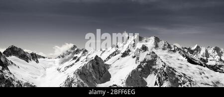 Panorama of snow-capped mountain peaks and sky with clouds at sun windy day. Caucasus Mountains in winter, region Dombay. Black and white toned landsc - Stock Photo
