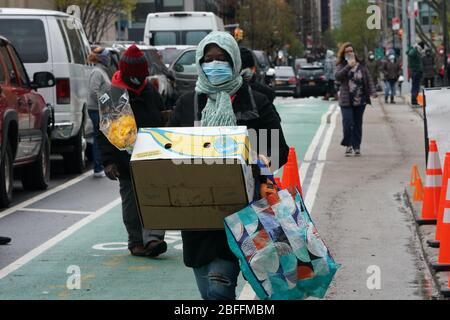 New York, NY, USA. 18th Apr, 2020. People pick up boxes with food donated by Trader Joe's at the Manor Community Church food bank during the COVID-19 pandemic on April 18, 2020 in New York. Credit: Bryan Smith/ZUMA Wire/Alamy Live News - Stock Photo