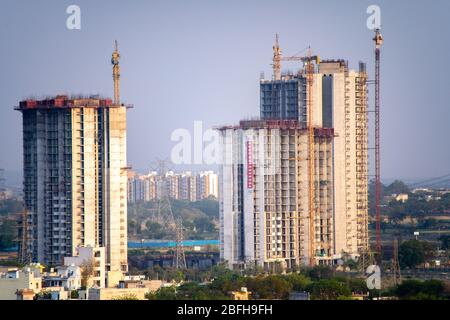Aerial shot of under construction building with multiple floors and crane at the top standing out in the countryside. Shows the rapid development of