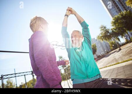 Morning exercises. Happy mature family couple in sportswear warming up together at outdoor gym in the morning, they are doing stretching exercises - Stock Photo