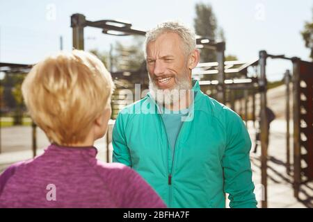 Active morning. Happy senior family couple is doing sport outdoors. Mature bearded man in sport wear talking with his wife while working out together - Stock Photo